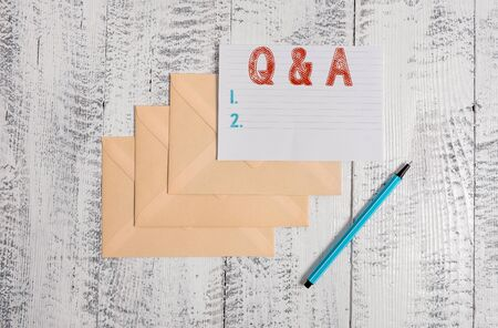 Text sign showing Q And A Question. Business photo showcasing in which demonstrating asks questions and another one answers them Three envelopes marker ruled paper sheet old wooden vintage background 版權商用圖片