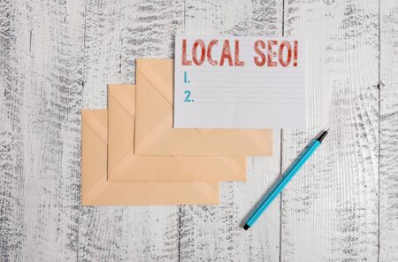 Text sign showing Local Seo. Business photo showcasing incredibly effective way to market your near business online Three envelopes marker ruled paper sheet old wooden vintage background