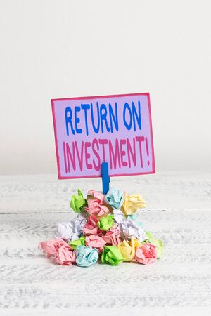 Conceptual hand writing showing Return On Investment. Concept meaning perforanalysisce measure used evaluate efficiency of investment Reminder pile colored crumpled paper clothespin wooden space Imagens - 128769414