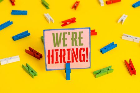 Word writing text We Re Hiring. Business photo showcasing recently employ someone or pay someone to do particular job Colored clothespin papers empty reminder yellow floor background office