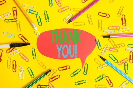 Word writing text Thank You. Business photo showcasing polite expression used when acknowledging gift service compliment Flat lay above empty paper with copy space pencils and colored paper clips Banco de Imagens