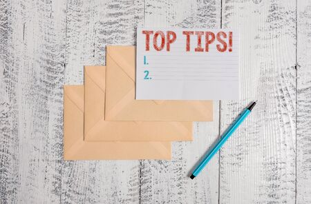 Text sign showing Top Tips. Business photo showcasing small but particularly useful piece of practical advice Three envelopes marker ruled paper sheet old wooden vintage background