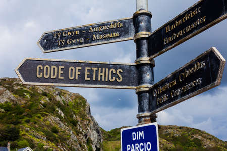 Word writing text Code Of Ethics. Business photo showcasing basic guide for professional conduct and imposes duties Road sign on the crossroads with blue cloudy sky in the background 스톡 콘텐츠