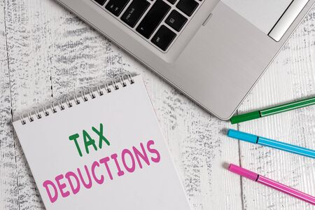 Word writing text Tax Deductions. Business photo showcasing an amount or cost that subtracted from someone s is income Top trendy metallic laptop blank spiral notepad pens lying wooden table Imagens - 128769248