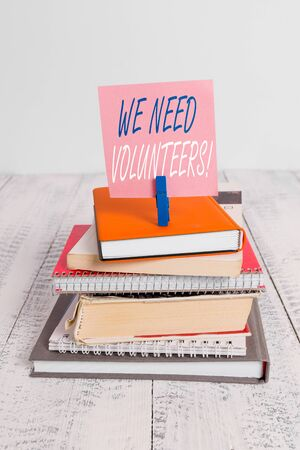Handwriting text We Need Volunteers. Conceptual photo someone who does work without being paid for it pile stacked books notebook pin clothespin colored reminder white wooden