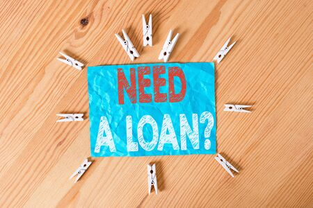 Word writing text Need A Loan Question. Business photo showcasing asking he need money expected paid back with interest Colored clothespin papers empty reminder wooden floor background office