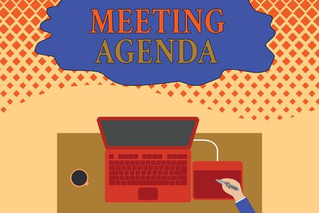 Writing note showing Meeting Agenda. Business concept for items that participants hope to accomplish at a meeting Upper view laptop wooden desk worker drawing tablet coffee cup office Banco de Imagens