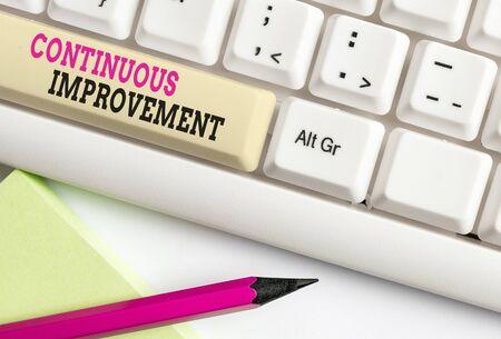 Wort schreiben Text Kontinuierliche Verbesserung. Geschäftsfoto, das die laufenden Bemühungen zur Verbesserung von Produkten oder Prozessen zeigt Weiße PC-Tastatur mit leerem Notizpapier über weißem Hintergrund-Tastenkopierraum