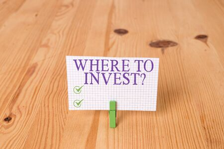 Writing note showing Where To Invest Question. Business concept for asking about where put money into financial schemes or shares Wooden floor background green clothespin groove slot office 写真素材