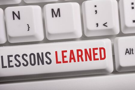 Text sign showing Lessons Learned. Business photo text the knowledge or understanding gained by experience White pc keyboard with empty note paper above white background key copy space