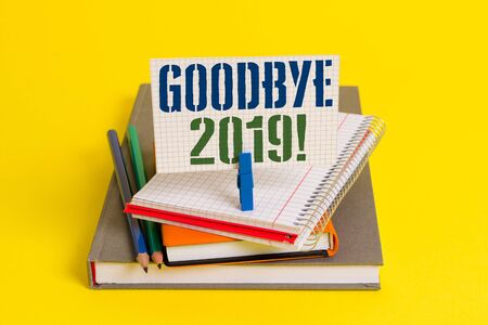 Writing note showing Goodbye 2019. Business concept for express good wishes when parting or at the end of last year Book pencil rectangle shaped reminder notebook clothespins