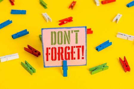 Word writing text Don T Forget. Business photo showcasing used to remind someone about important fact or detail Colored clothespin papers empty reminder yellow floor background office Stock Photo