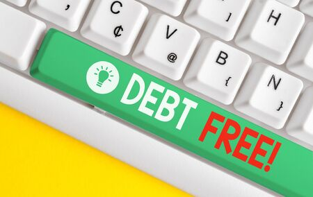 Text sign showing Debt Free. Business photo text does not owning any money or things to any individual or companies White pc keyboard with empty note paper above white background key copy space