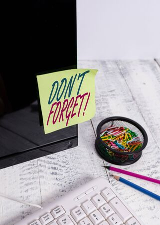 Text sign showing Don T Forget. Business photo text used to remind someone about important fact or detail Note paper taped to black computer screen near keyboard and stationary