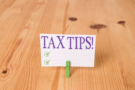 Writing note showing Tax Tips. Business concept for compulsory contribution to state revenue levied by government Wooden floor background green clothespin groove slot office