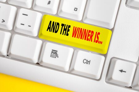 Text sign showing And The Winner Is. Business photo text announcing a demonstrating or thing that wins something White pc keyboard with empty note paper above white background key copy space 写真素材