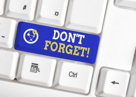 Conceptual hand writing showing Don T Forget. Concept meaning used to remind someone about important fact or detail White pc keyboard with note paper above the white background