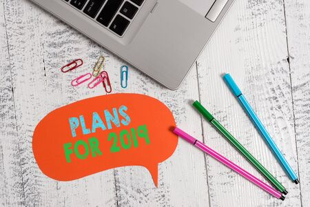 Handwriting text Plans For 2019. Conceptual photo an intention or decision about what one is going to do Trendy metallic laptop speech bubble colored clips pens lying vintage table