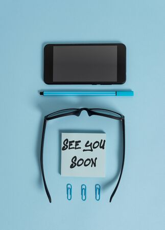 Writing note showing See You Soon. Business concept for used for saying goodbye to someone and going to meet again soon Dark eyeglasses colored sticky note smartphone pen pastel background