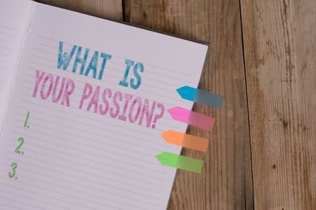 Text sign showing What Is Your Passion Question. Business photo text asking about his strong and barely controllable emotion Striped note book four colored arrow banners reminder wooden background