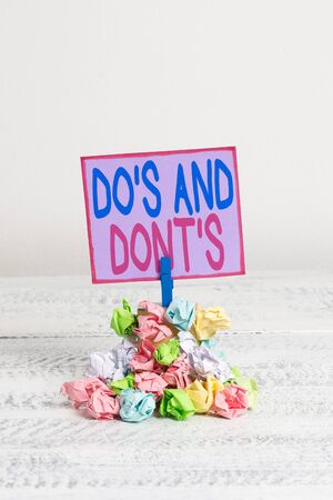 Conceptual hand writing showing Do S And Dont S. Concept meaning Rules or customs concerning some activity or actions Reminder pile colored crumpled paper clothespin wooden space Foto de archivo - 128929088