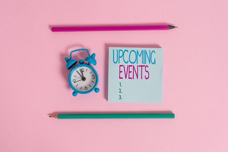 Handwriting text Upcoming Events. Conceptual photo the approaching planned public or social occasions Metal vintage alarm clock wakeup blank notepad markers colored background