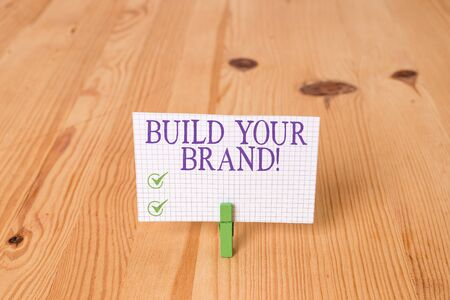 Writing note showing Build Your Brand. Business concept for creates or improves customers knowledge and opinions of product Wooden floor background green clothespin groove slot office