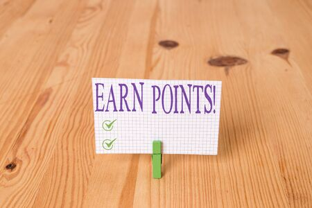 Writing note showing Earn Points. Business concept for collecting scores in order qualify to win big prize Wooden floor background green clothespin groove slot office 写真素材