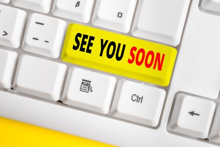 Text sign showing See You Soon. Business photo text used for saying goodbye to someone and going to meet again soon White pc keyboard with empty note paper above white background key copy space Stock Photo