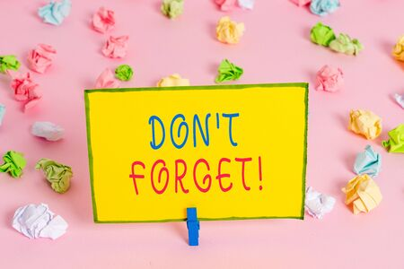 Word writing text Don T Forget. Business photo showcasing used to remind someone about an important fact or detail Colored crumpled papers empty reminder pink floor background clothespin Stock Photo