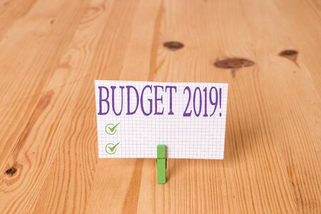 Writing note showing Budget 2019. Business concept for estimate of income and expenditure for current year Wooden floor background green clothespin groove slot office 写真素材