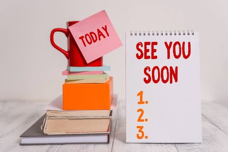 Word writing text See You Soon. Business photo showcasing used for saying goodbye to someone and going to meet again soon Cup sticky note stacked note pads books square box spiral wooden table