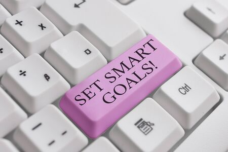 Conceptual hand writing showing Set Smart Goals. Concept meaning list to clarify your ideas focus efforts use time wisely White pc keyboard with note paper above the white background