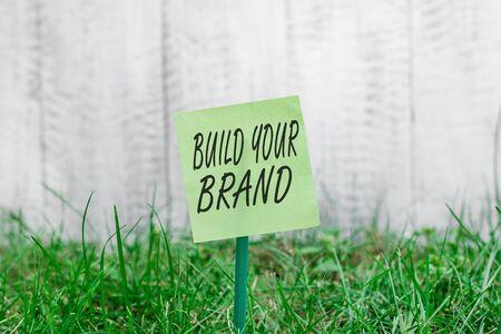 L'écriture de texte Word Construisez votre marque. Photo d'entreprise présentant l'amélioration de la valeur de la marque à l'aide de campagnes publicitaires Papier vide ordinaire attaché à un bâton et placé dans les terres herbeuses vertes