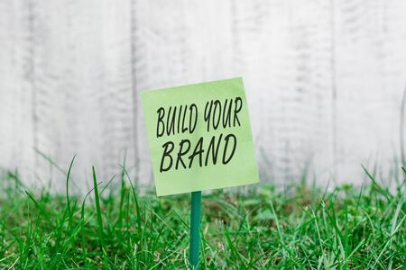 Word writing text Build Your Brand. Business photo showcasing enhancing brand equity using advertising campaigns Plain empty paper attached to a stick and placed in the green grassy land