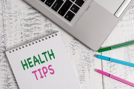 Word writing text Health Tips. Business photo showcasing advice or information given to be helpful in being healthy Top trendy metallic laptop blank spiral notepad pens lying wooden table Stockfoto