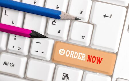 Word writing text Order Now. Business photo showcasing the activity of asking for goods or services from a company White pc keyboard with empty note paper above white background key copy space Stock Photo