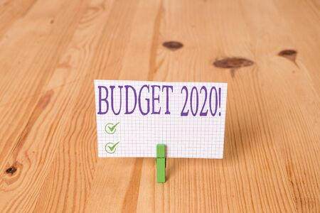 Writing note showing Budget 2020. Business concept for estimate of income and expenditure for next or current year Wooden floor background green clothespin groove slot office