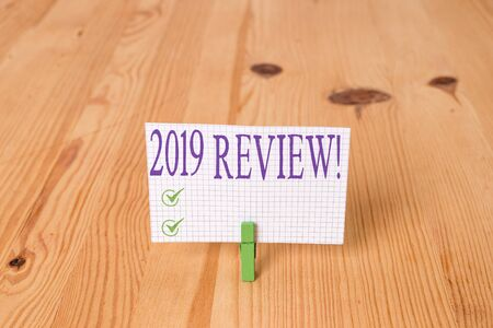 Writing note showing 2019 Review. Business concept for remembering past year events main actions or good shows Wooden floor background green clothespin groove slot office