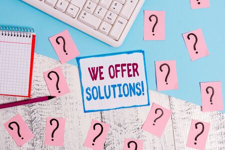 Writing note showing We Offer Solutions. Business concept for way to solve problem or deal with difficult situation Writing tools and scribbled paper on top of the wooden table 写真素材