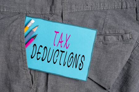 Conceptual hand writing showing Tax Deductions. Concept meaning an amount or cost that subtracted from someone s is income Writing equipment and blue note paper in pocket of trousers