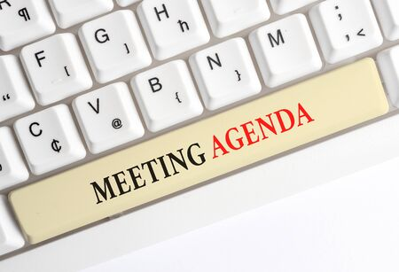 Writing note showing Meeting Agenda. Business concept for items that participants hope to accomplish at a meeting White pc keyboard with note paper above the white background