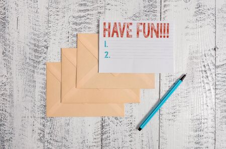Text sign showing Have Fun. Business photo showcasing wish somebody good and enjoyable time when they do something Three envelopes marker ruled paper sheet old wooden vintage background