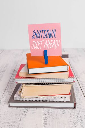 Handwriting text Shutdown Just Ahead. Conceptual photo closing factory business either short time or forever pile stacked books notebook pin clothespin colored reminder white wooden