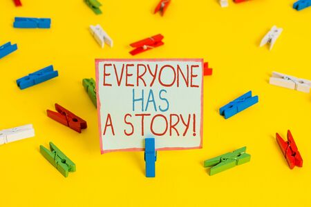 Conceptual hand writing showing Everyone Has A Story. Concept meaning account of past events in someones life or career Colored clothespin papers empty reminder yellow floor office Zdjęcie Seryjne