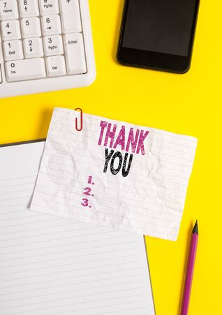 Text sign showing Thank You. Business photo text a polite expression used when acknowledging a gift or service Crumpled white paper on table with paper clips clock mobile and pc keyboard Zdjęcie Seryjne