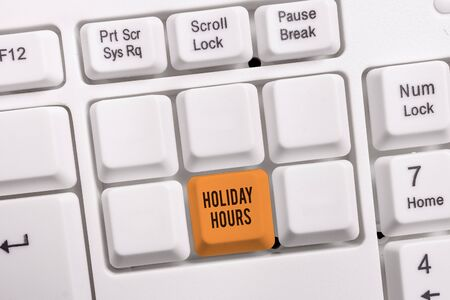Conceptual hand writing showing Holiday Hours. Concept meaning employee receives twice their normal pay for all hours White pc keyboard with note paper above the white background