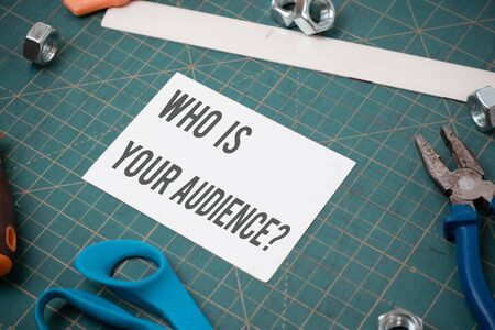 Writing note showing Who Is Your Audience Question. Business concept for who is watching or listening to it Stationary and carpentry tools with paper above a textured backdrop