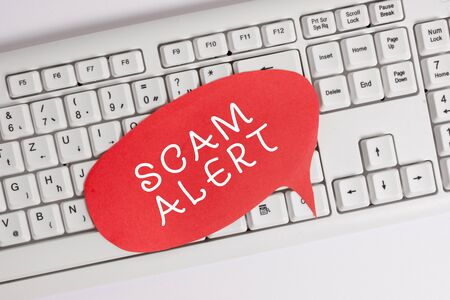 Handwriting text writing Scam Alert. Conceptual photo unsolicited email that claims the prospect of a bargain Empty copy space red note paper bubble above pc keyboard for text message