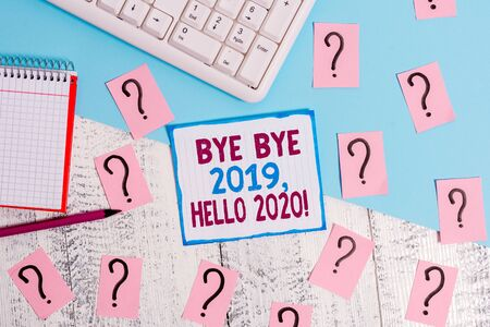 Writing note showing Bye Bye 2019 Hello 2020. Business concept for saying goodbye to last year and welcoming another good one Writing tools and scribbled paper on top of the wooden table